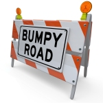 The words Bumpy Road on a barrier or blockade as a warning sign